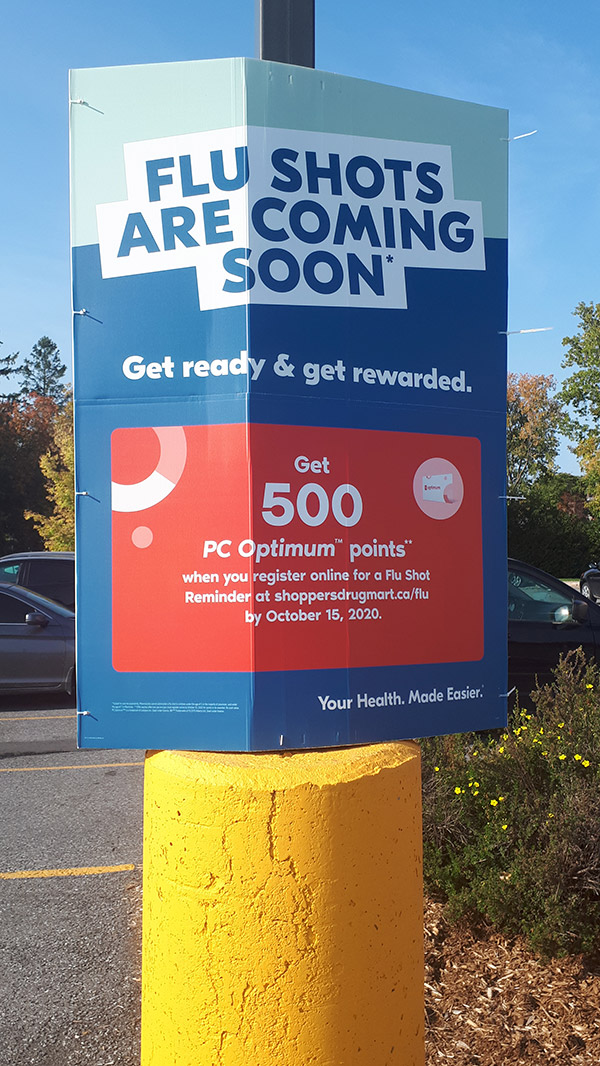 "A sign in a parking lot that reads ""flu shots are coming soon""."