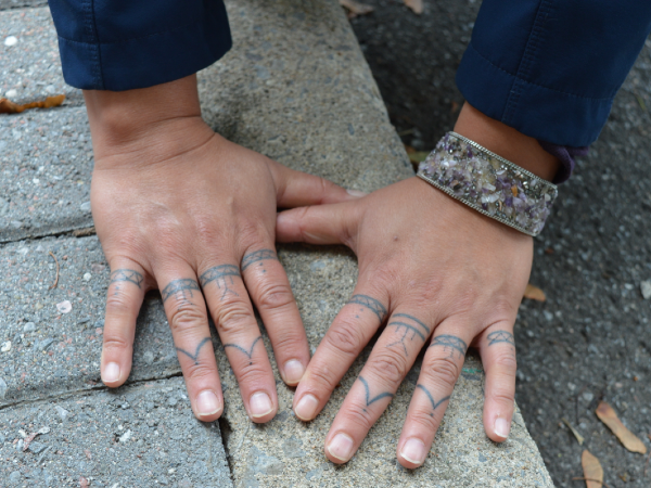 Heidi Langille flattens her hands on a cement curb to show off her traditional Inuit tattoos that her niece did for her using the stick and poke technique.