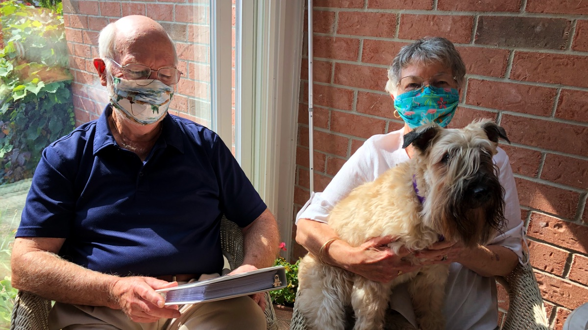 Two seniors, a man and a woman, sit on their patio. They are wearing masks. The man is looking at the cover of a photo album. The woman has a wheaten terrier on her lap.