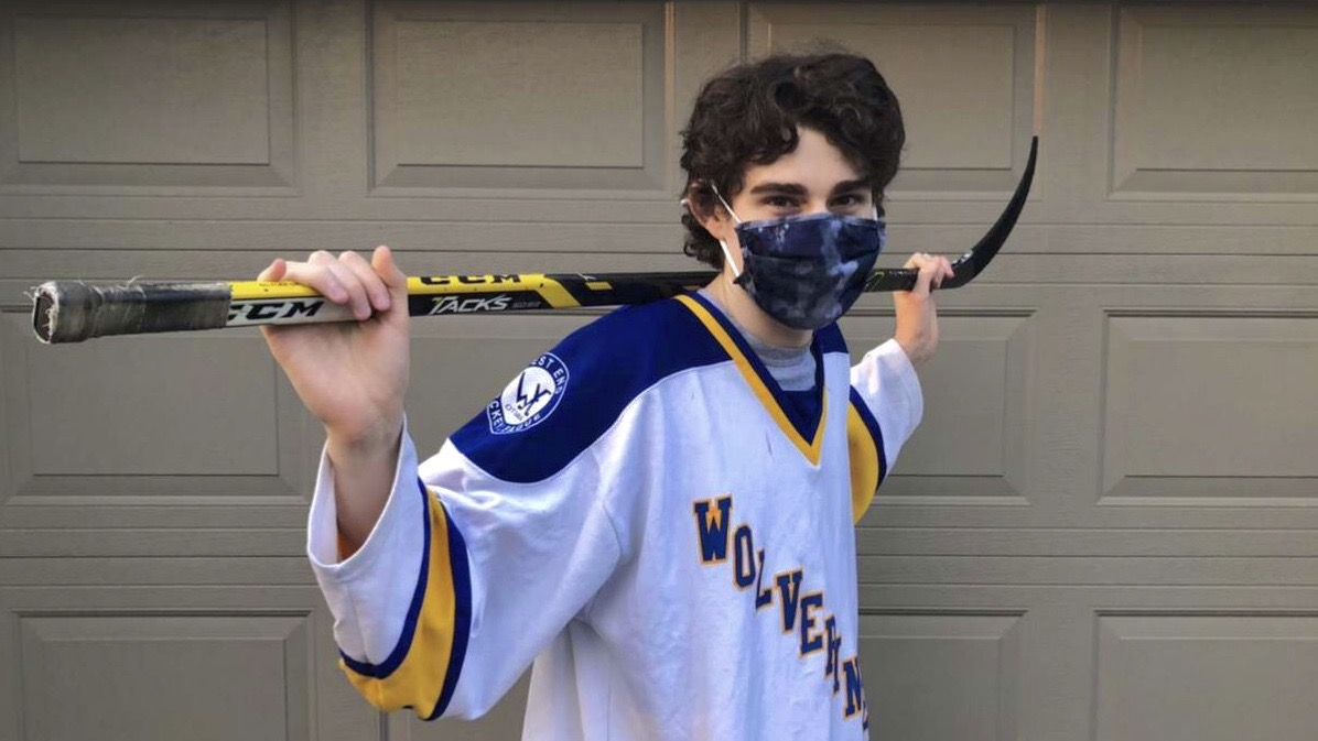 Danny Gaudet stands with his hockey stick and his face mask on.