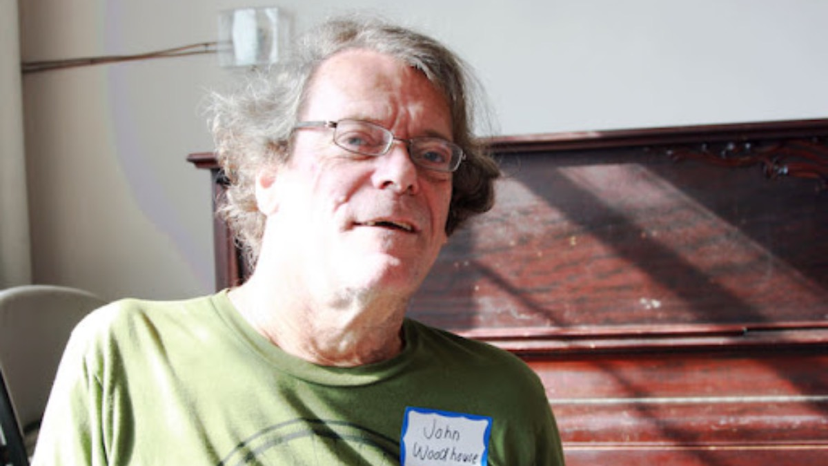 Close-up photo of John Woodhouse wearing a green shirt, glasses, and a nametag.