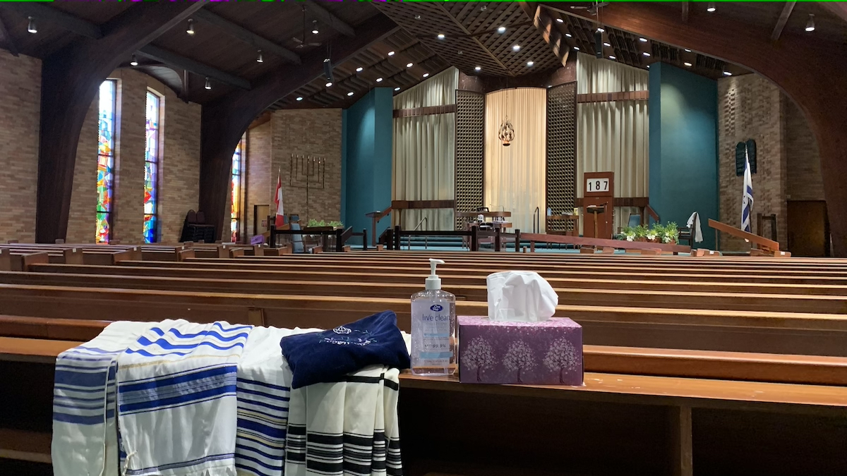 Prayer shawls drawn over empty pews alongside a tissue box and hand sanitizer at Kehillat Beth Israel synagogue.