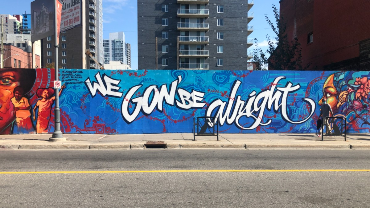 """A long mural is shown from across the street. The words """"We Gon' Be Alright"""" in white stretch across a blue background. On either side of the words are women painted in golden tones."""