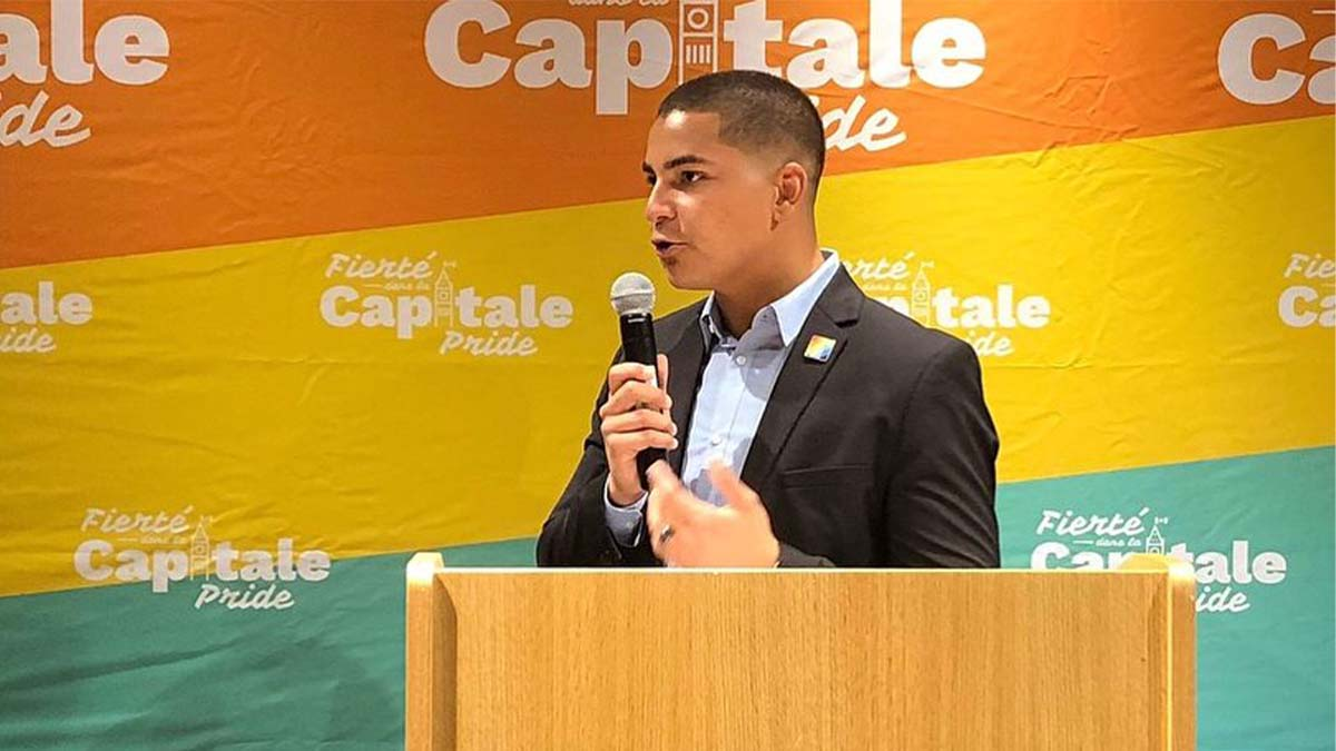 A photo of Davy Sabourin, Capital Pride's chairperson on the Board of Directors standing at a podium and holding a microphone behind a Capital Pride banner.