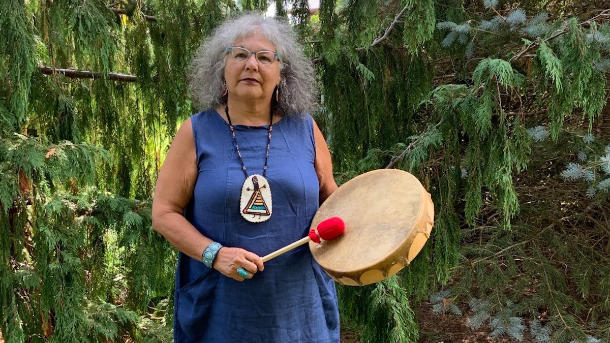 Lorraine Whitman stands with a drum.
