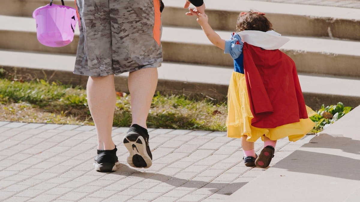 A child holds their parents' hand on their way to go trick or treating