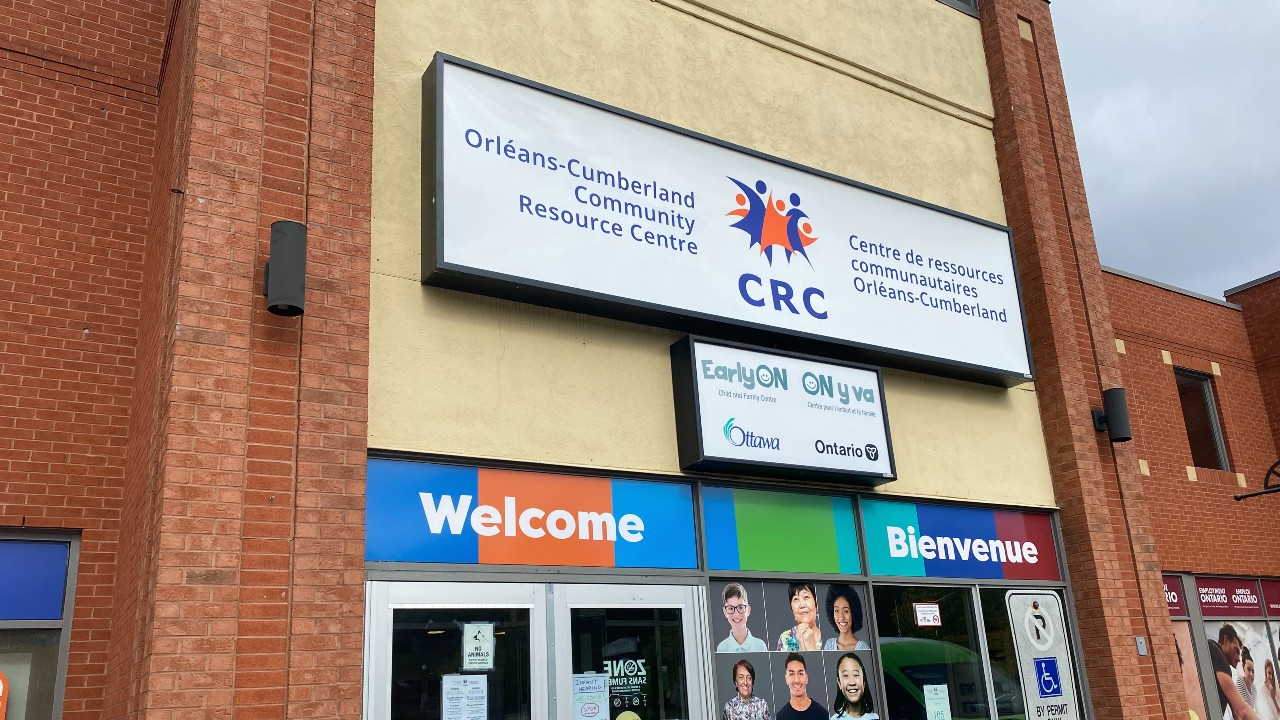 "Front entrance of the Orléans-Cumberland Community resource centre, with a sign above the door saying ""Orléans-Cumberland Community Resource Centre/Centre de resources communautaires Orléans-Cumberland,"" and a bilingual welcome sign below."