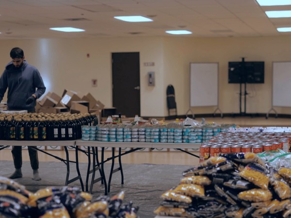 Momin Janjua stands at a table and is packaging boxes, with food supplies in the back and foreground.