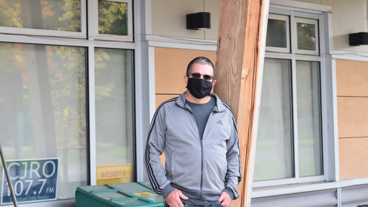 Denis LaBreche standing outside the Carlsbad Springs Community Centre, with his hands in his pockets and wearing a mask.