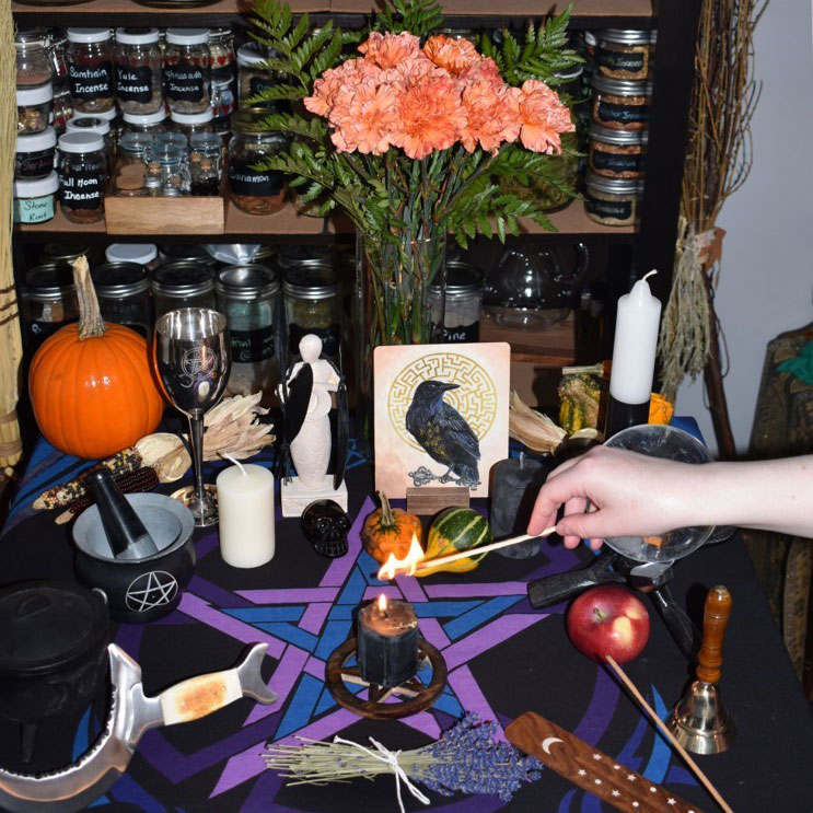 eclectic photo of an altar containing: a black light candle, lavender, an apple, picture of crow, among other things.