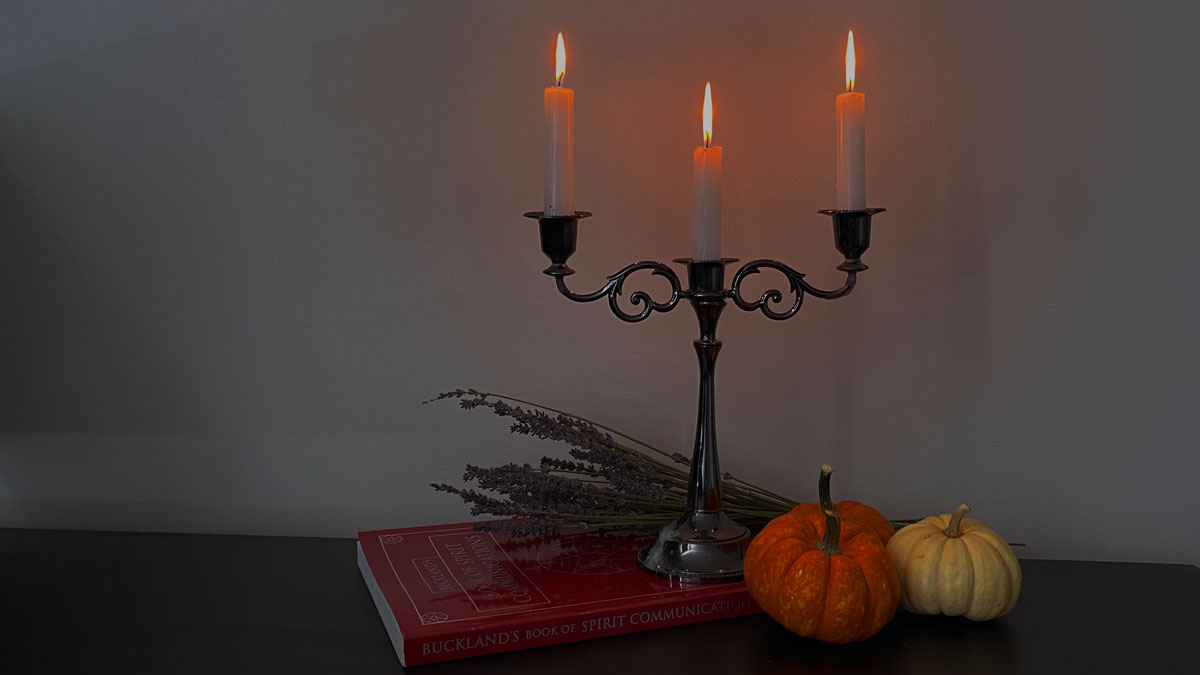 3 tier candles alongside pumpkins, lavender and a book on spirit communication.
