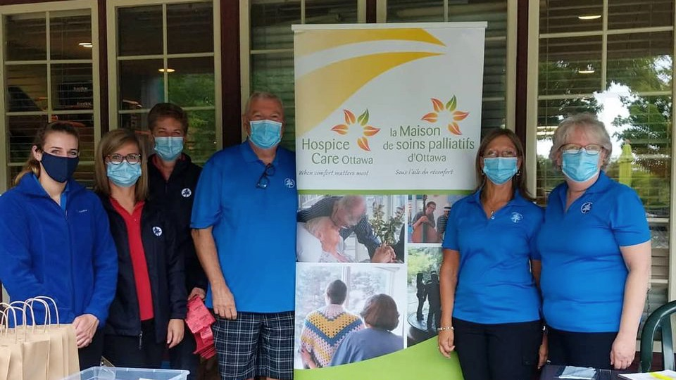 Six people stand in front of a Hospice Care Ottawa banner. They are wearing masks and blue shirts.