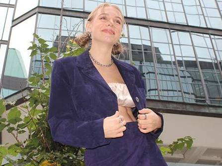 Woman wearing a blue jacket and skirt in front of buildings.