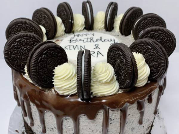 a birthday cake rounded in chocolate drip and Oreo cookies.