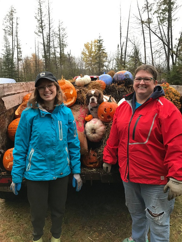 Two women standing next to each other in front of a truck filled with pumpkins.