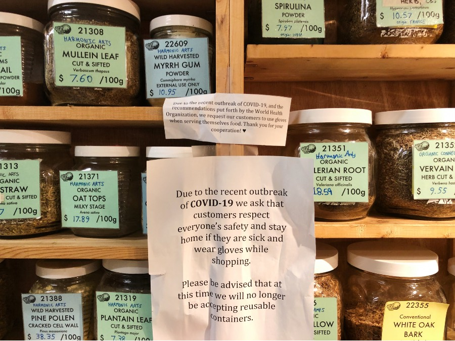 Low waste grocery store 'Herb and Spice Shop' sign posted on their self serving spice shelf describing why they no longer allow customers to bring in their own containers due to pandemic.