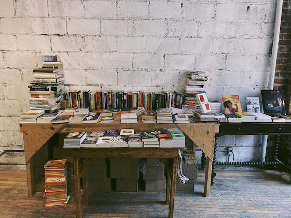 Three desks covered in books against a white brick wall.