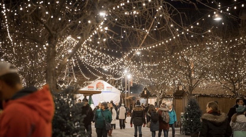 This photo showcases the Ottawa Christmas Market last year, as crowds walk under an array of Christmas lights, passing vendors in wooden huts.