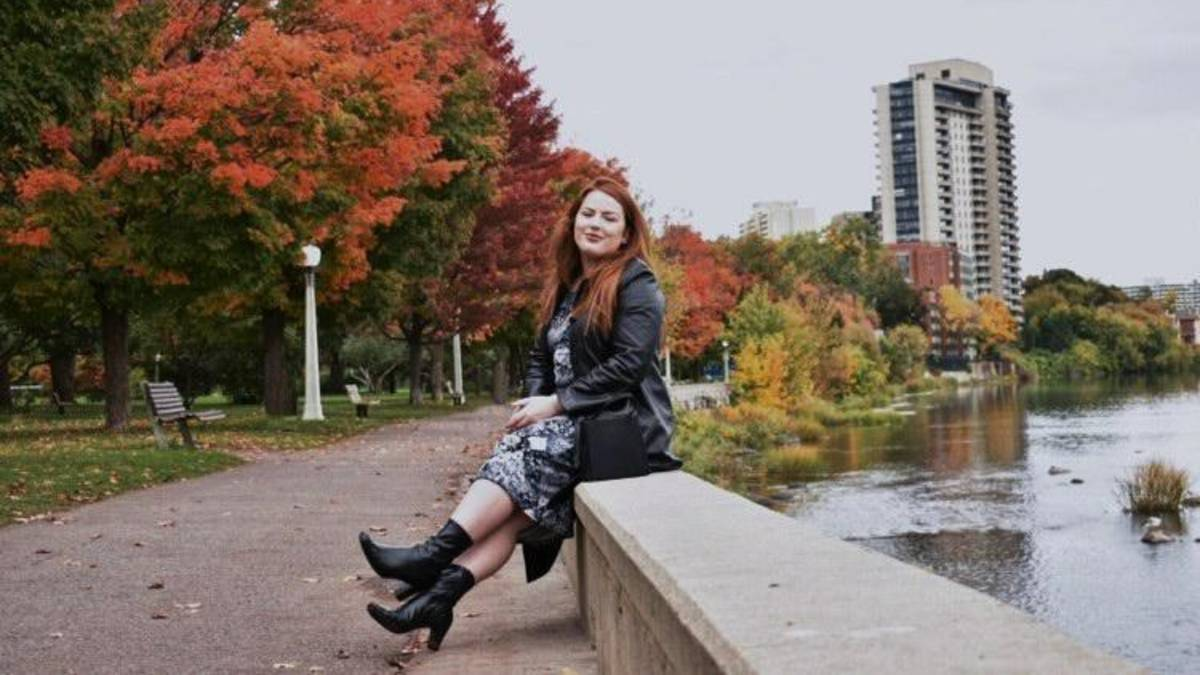 Kiana Seitz sits by the Rideau Canal with fall trees in the background.
