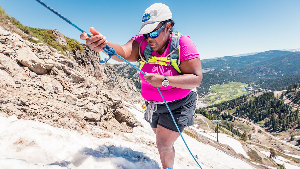 A woman in a pink shirt holds a rope to climb a steep mountain.