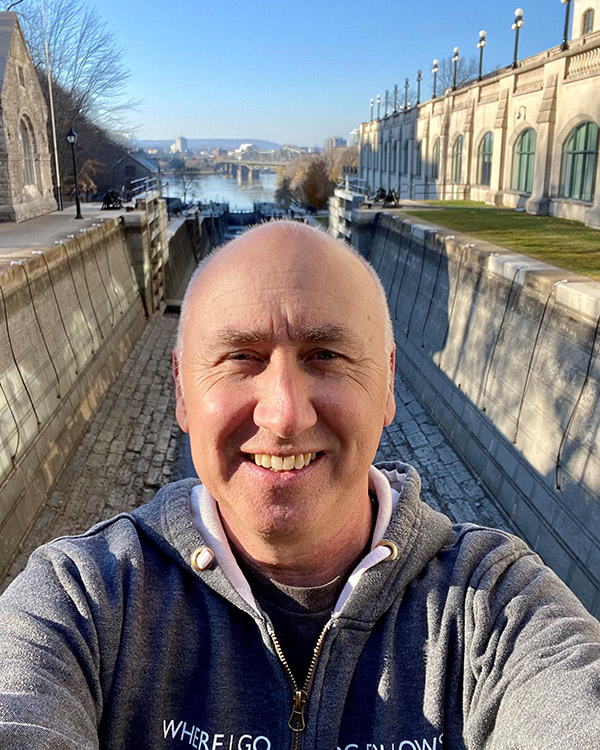 Kelvin Stanke smiles for a selfie by the Rideau Canal in Ottawa.