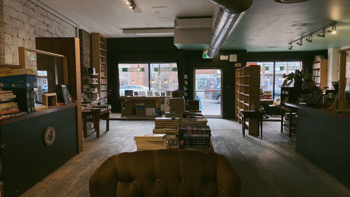 Front space of Black Squirrel Books, with counters on right and left, a long table with books down the middle with aisles on either side, and front store windows at the back of the photograph.
