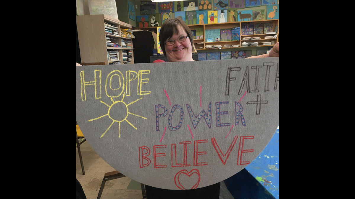 "Photo of Analisa Kiskis holding a banner that says ""HOPE POWER FAITH+BELIEVE ME"""