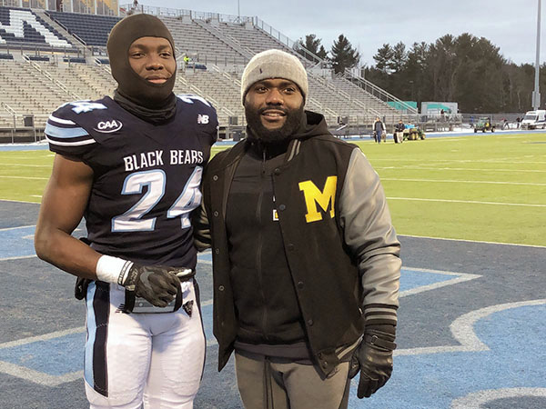 Jean Guillaume and former player Katley Joseph, pose for a photo at the University of Maine football field.