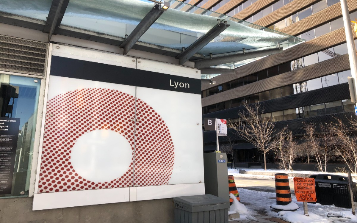 A photo of the sign outside of the Lyon LRT station, with snow on the ground