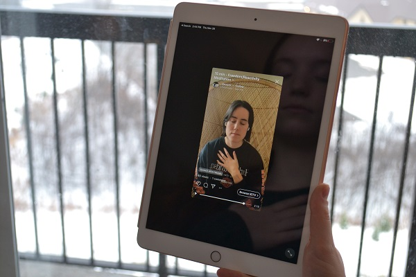 Girl holding an iPad and meditating to a guided meditation video.
