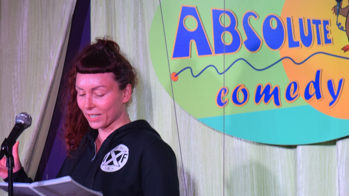 Woman reading stand-up material on stage.