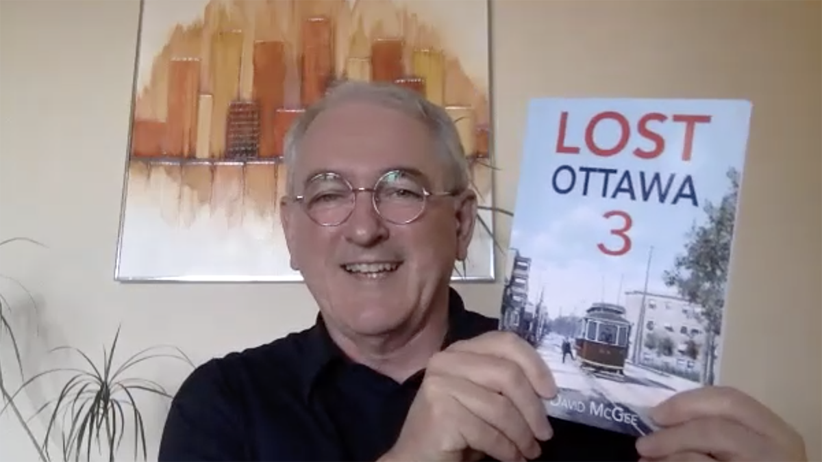 David McGee, author of Lost Ottawa 3, holds up a copy of Lost Ottawa 3 while smiling.