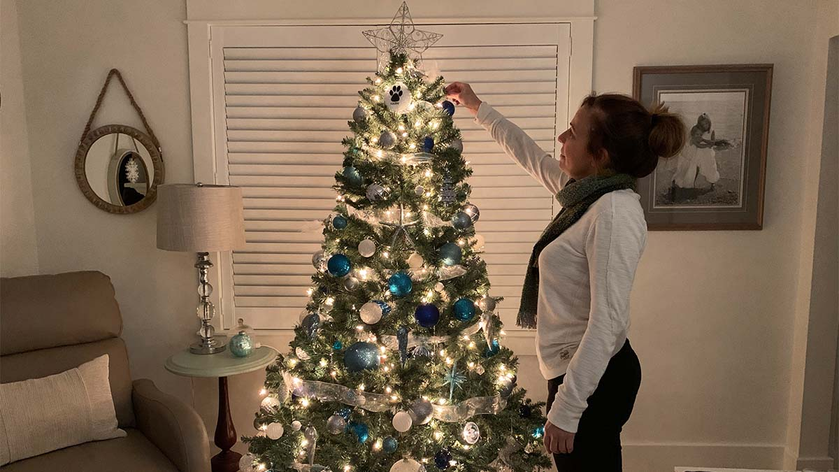 Woman putting an ornament on a Christmas tree.