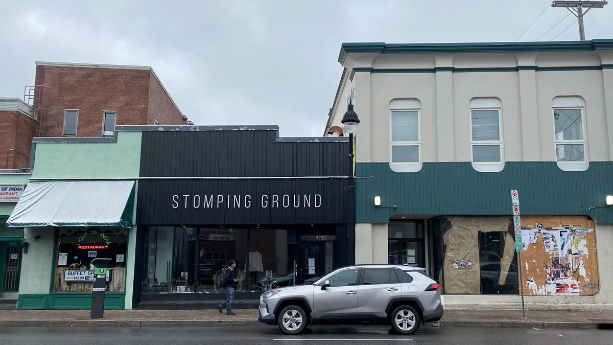 Picture of storefronts at Bank and First Street Intersection. Stores (from left to right) are: LIght of Idea, Stomping Ground, third store is bordered up and empty.
