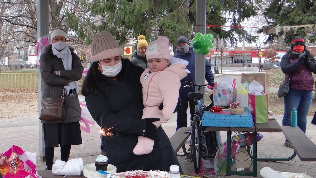 A birthday party is held outside for a young refugee girl.