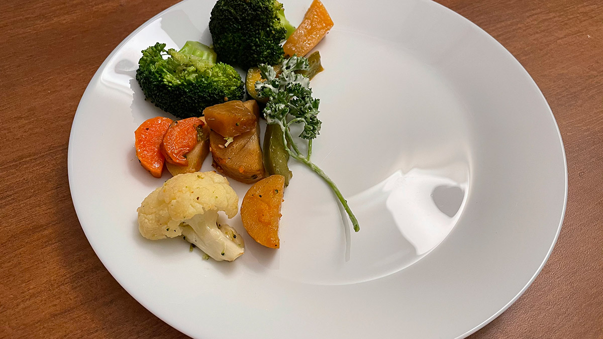A half-empty plate with assorted vegetables on it.