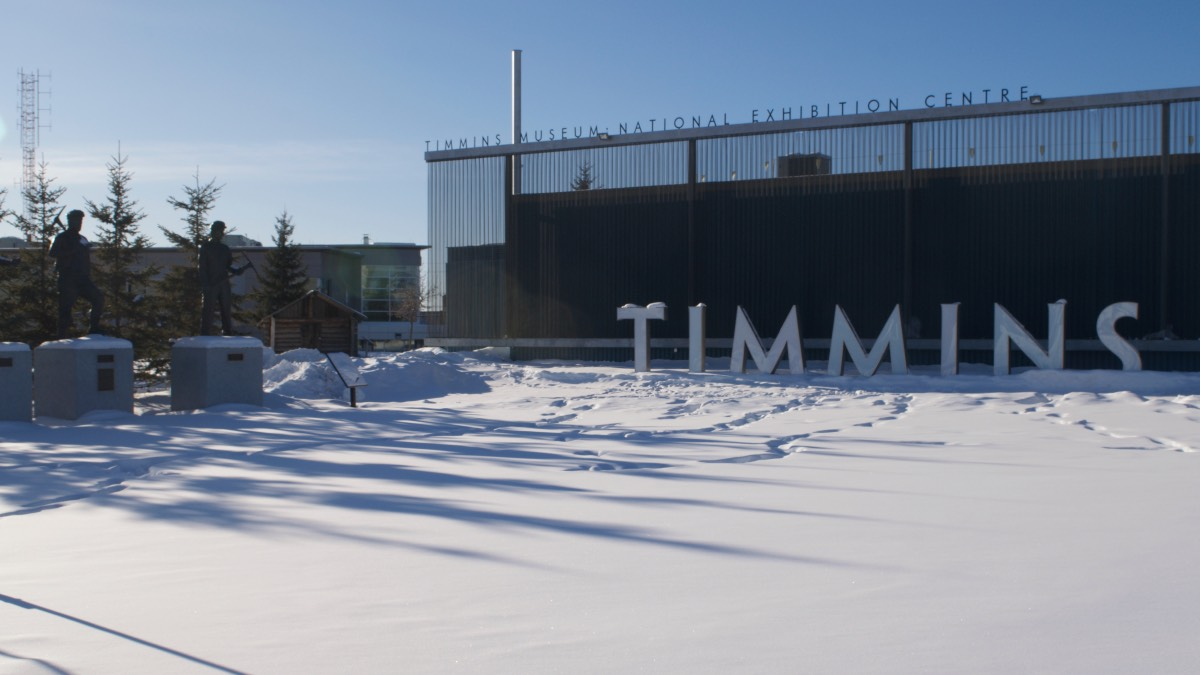 Large white letters spelling out Timmins in front of the Timmins Museum.