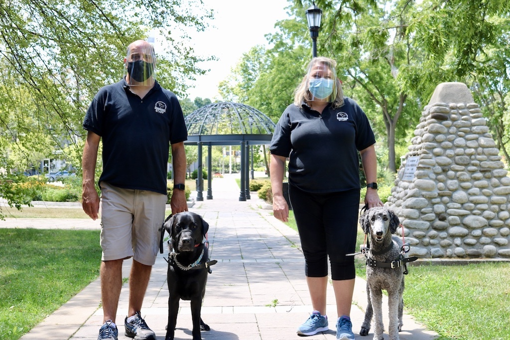 Two Lions Foundation dog trainers, wearing surgical face masks and plastic face shields, pose in an outdoor park setting with two guide dogs standing leashed at their sides.
