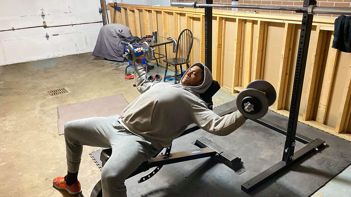 football player lifts weights in garage