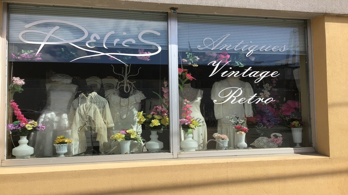 Various vintage white dresses posed in a store front window.