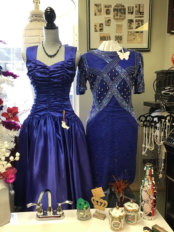 Two vintage dresses on dress mannequins surrounded by various other antiques and collectables.