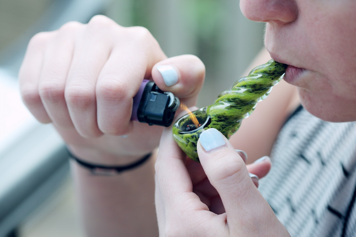 A cannabis user is smoking from a pipe.