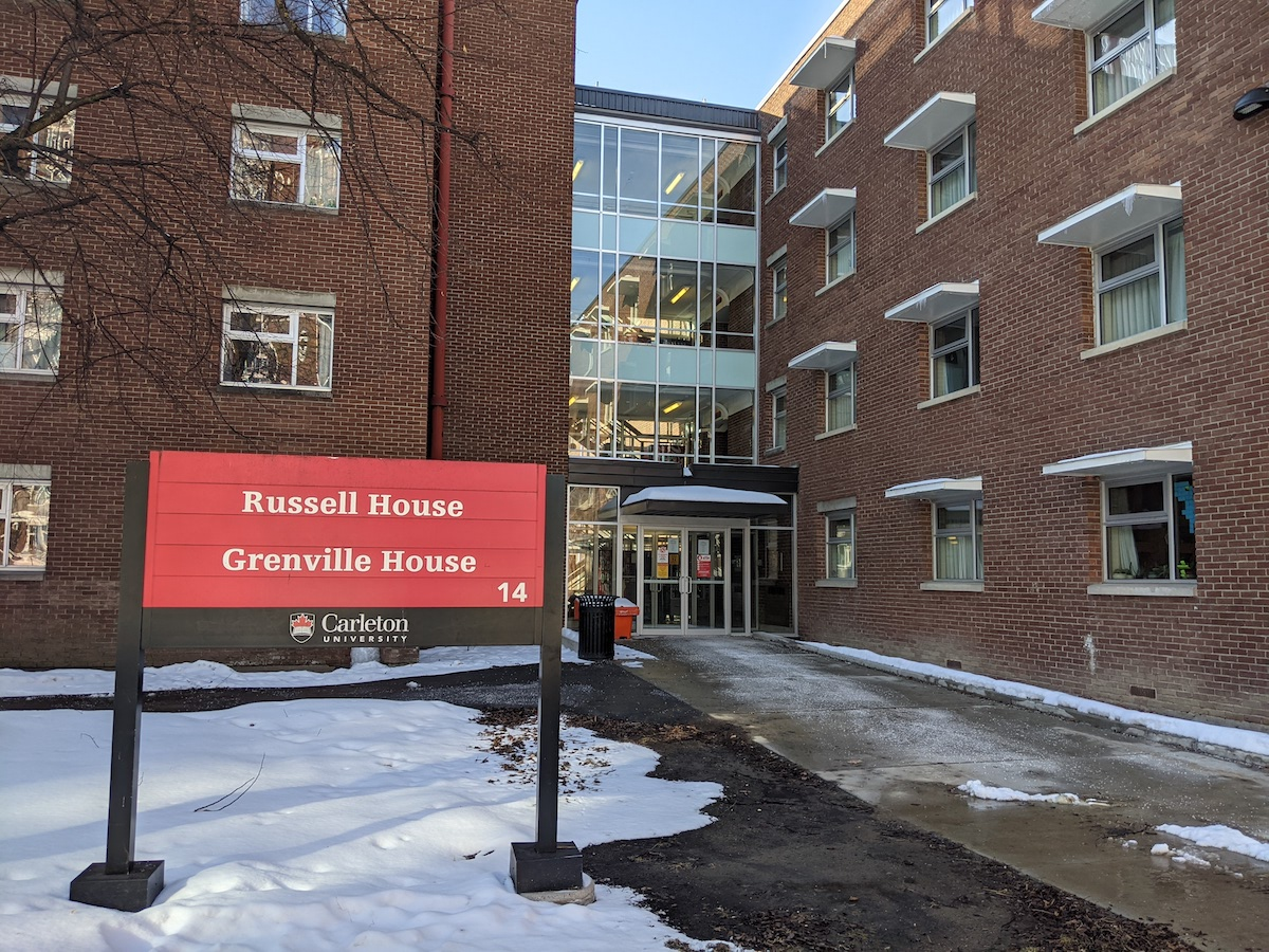 Student residence building Russell House is pictured beside the campus sign designating the building.