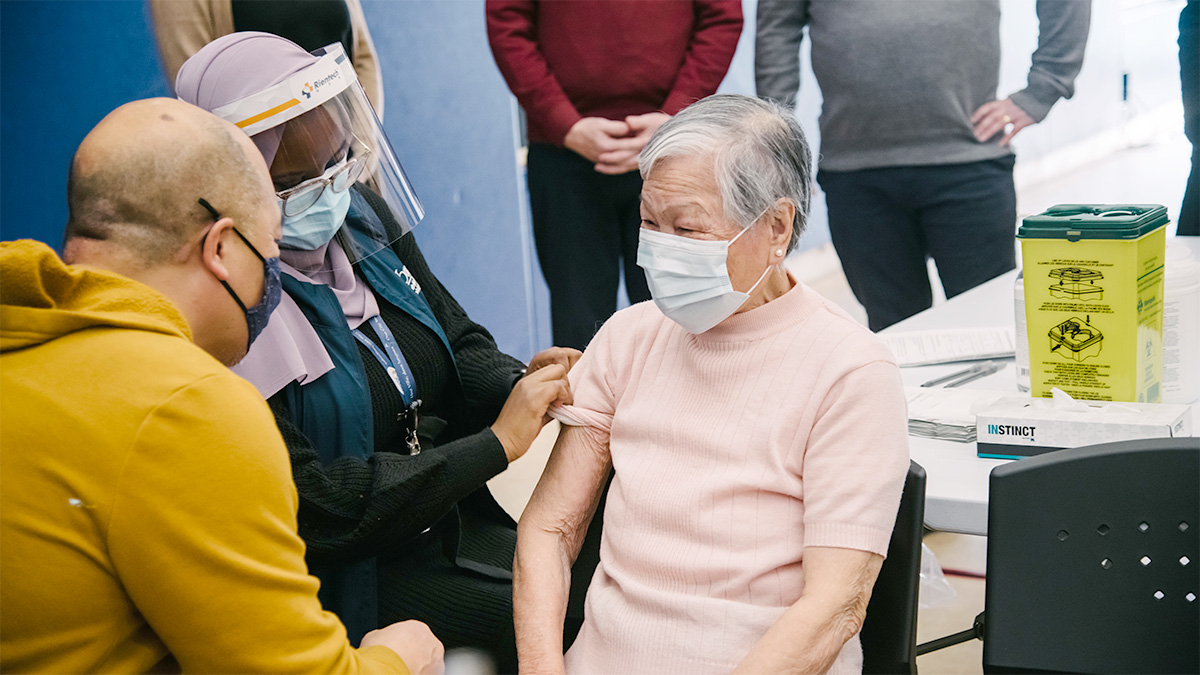 An elderly woman gets vaccinated.