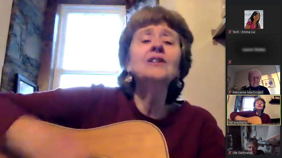 A woman strums a guitar on a zoom call.