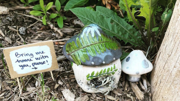 """A clay mushroom sculpture hidden within some greenery, and a small sign that reads """"Bring me home with you please!""""."""