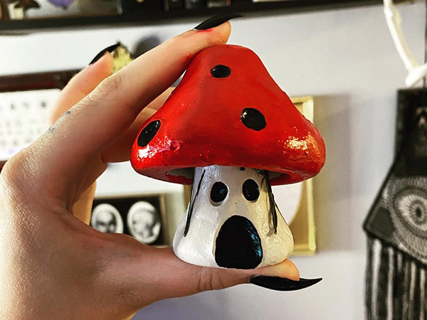 A hand with black fingernail polish holds up a small toadstool sculpture, painted white, red and black.