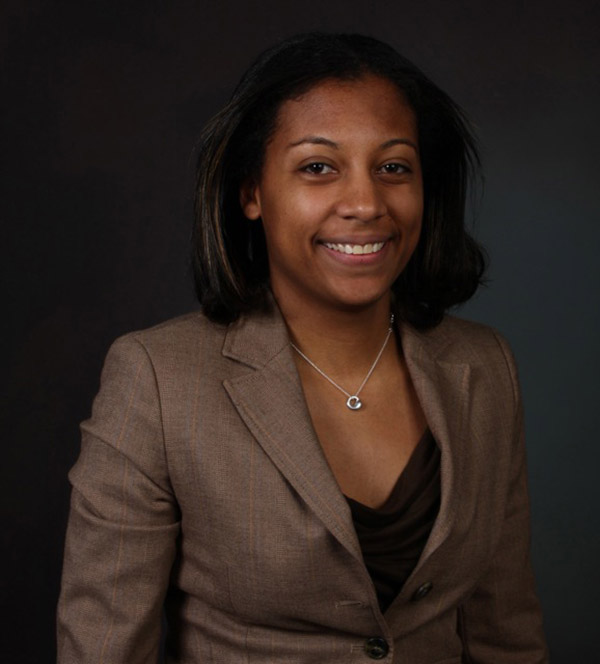 A woman wearing a brown suit smiles and stands in front of a grey background.