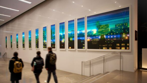 People walk through a hallway lined with digital displays of art.