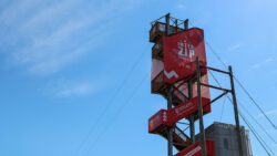 """A zipline launch tower with a red banner that says """"Interzip Rogers""""."""